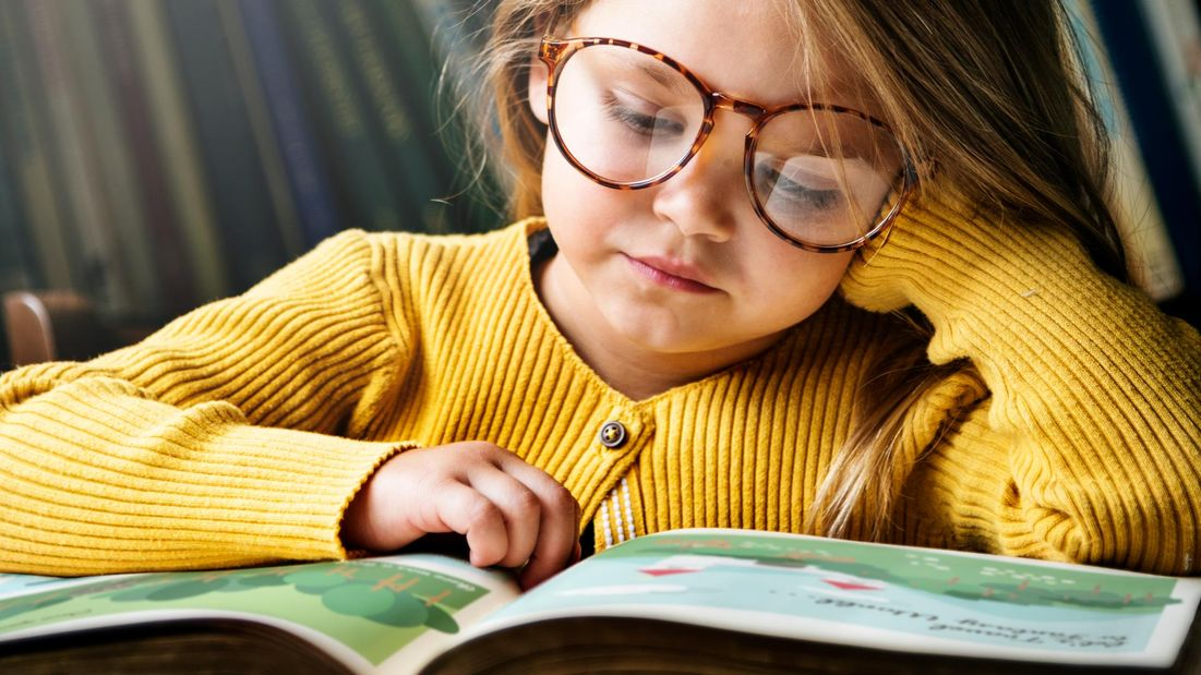 A young girl with glasses reading a book